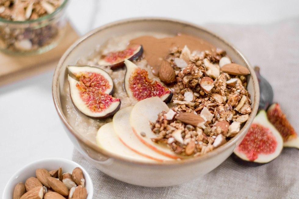Auf diesem Bild ist ein veganes und zuckerfreies Apfel - Zimt Granola zu sehen. Das Granola wurde auf einem Mandelporridge angerichtet mit Mandelmus und Feigen.