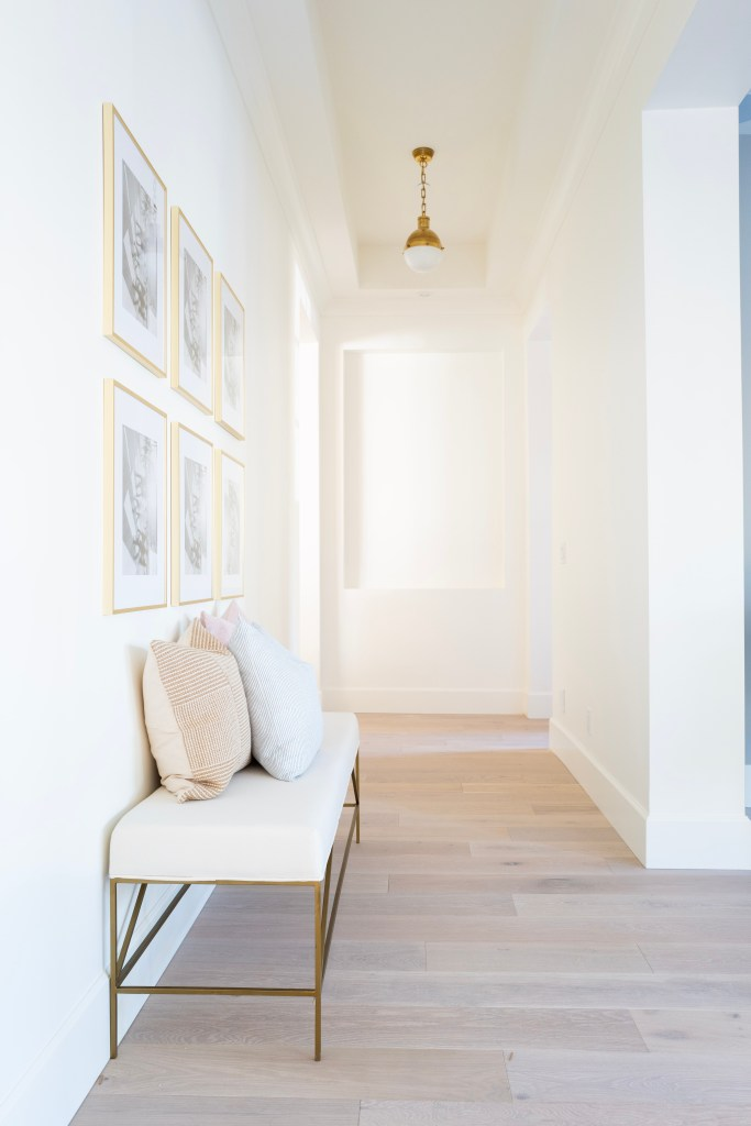 NEUTRAL OTTOMANS & BENCHES by popular interior design blog, E. Interiors: image of a white and gold bench with pastel throw pillows in a hallway.
