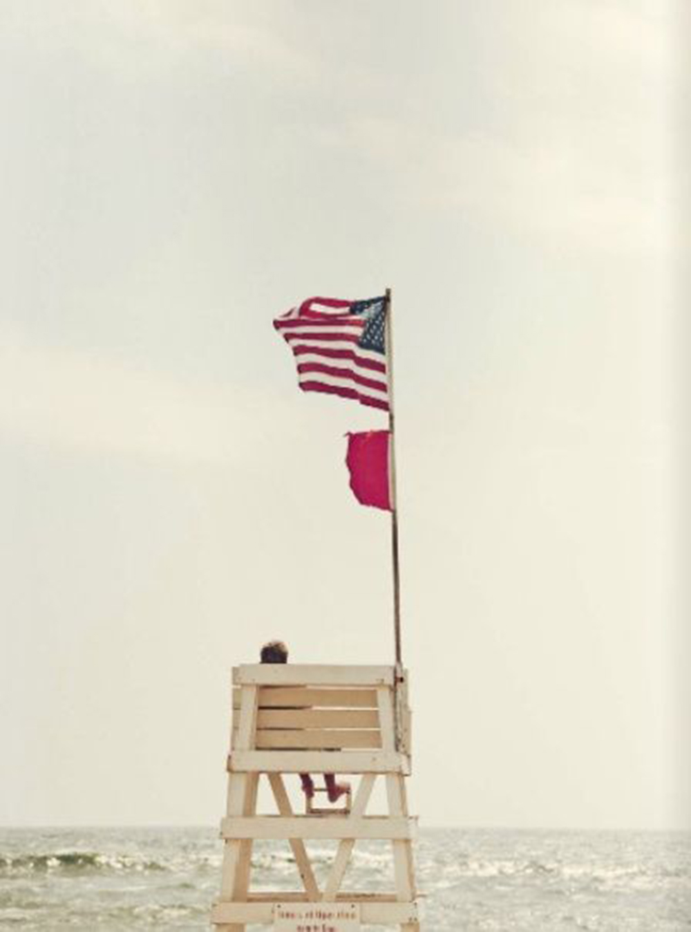 Best 4th of July Sales popular interior design blog, E. Interiors: image of white lifeguard tower with an American flag at the beach.