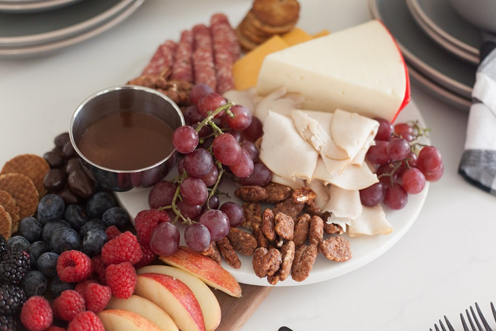 WALMART HOLIDAY ESSENTIALS by popular style blog, E. Interiors: image of a charcuterie board, DII Buffalo Check Kitchen Napkin Set, and Better Homes & Gardens Zuri Matte 12-Piece Dinnerware Set from Walmart.
