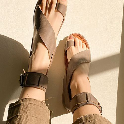 Spring Sandals by popular design blog, E. Interiors Design: image of a woman wearing brown strap sandals.
