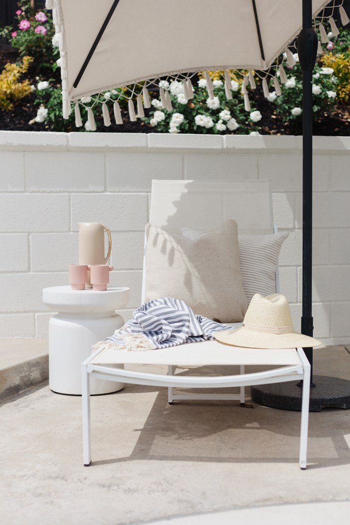 Summer Essentials From Walmart by popular US interior design blog, E. Interiors: image of a grey and white striped Turkish towel on a white lounge chair next to a straw white and white end table with two pink cups and a cream ceramic pitcher.
