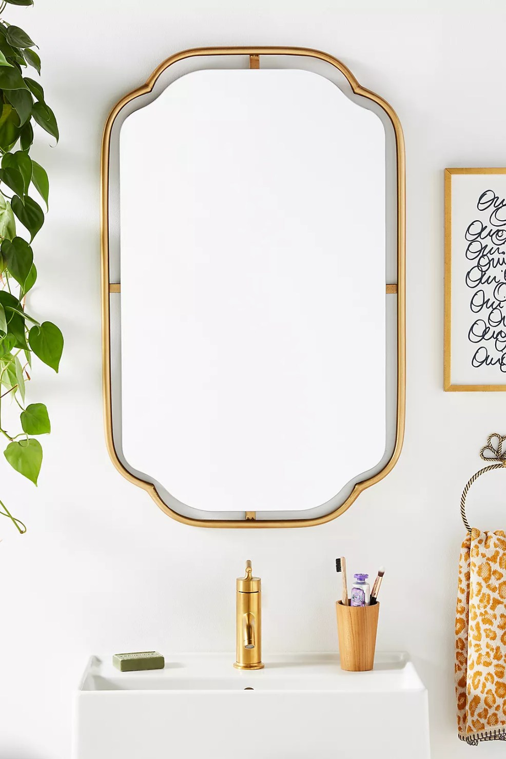 Anthropologie Bathroom by popular US interior design blog, E. Interiors Design: image of a bathroom with a gold mirror, white sink with a gold sink faucet, leopard print towel on a black and gold towel ring, and a wood cup filled with a toothbrush, lotion, and makeup brush.