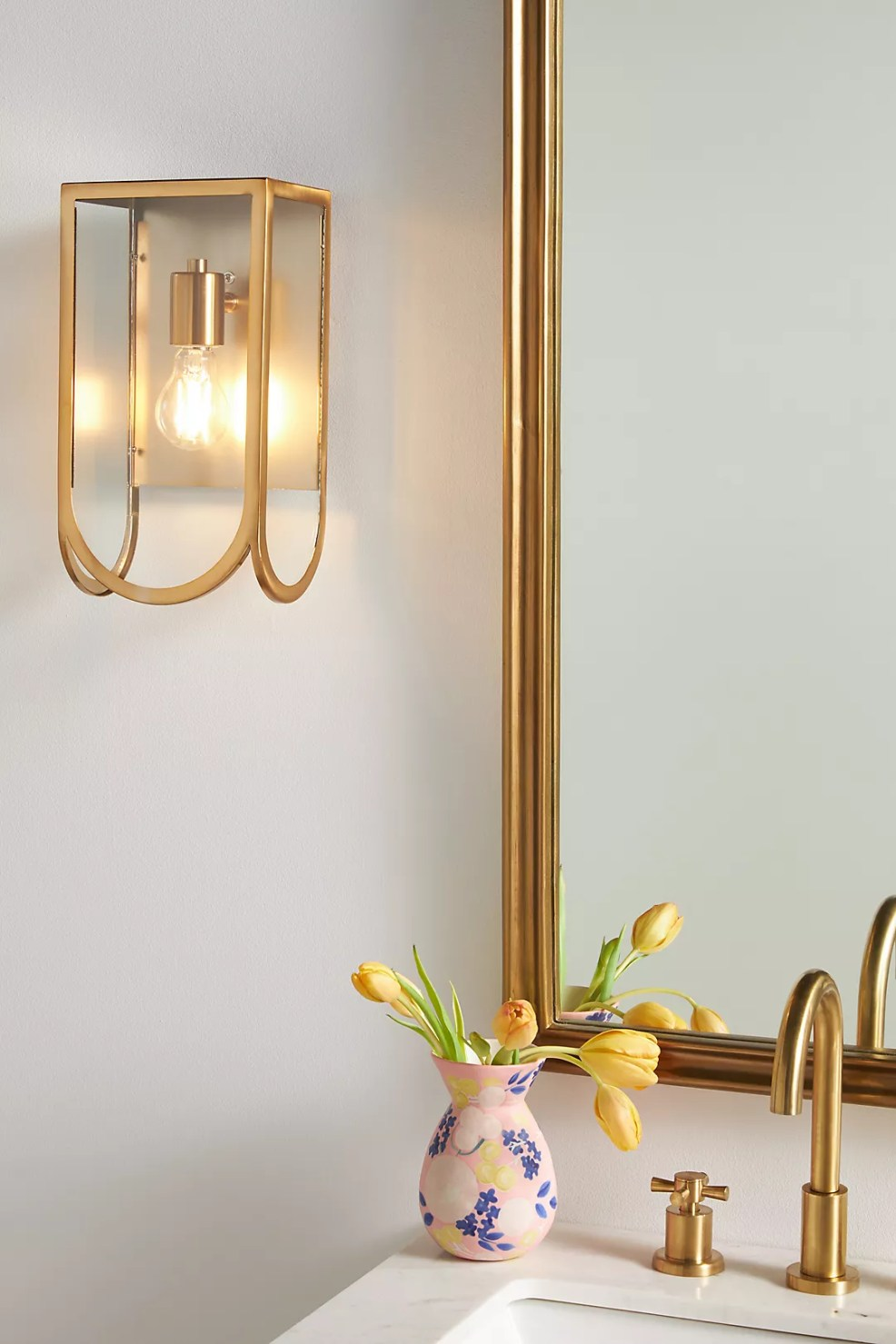 Anthropologie Bathroom by popular US interior design blog, E. Interiors Design: image of a bathroom with gold frame mirror, white sink with gold faucet, gold sconce lighting, and a pink and blue floral vase filled with yellow tulips.