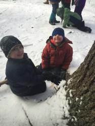 Two kindergarteners dig for squirrel food.