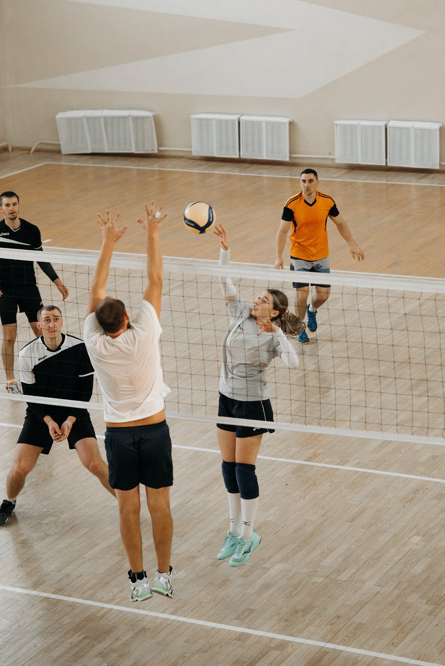 women playing volleyball on court