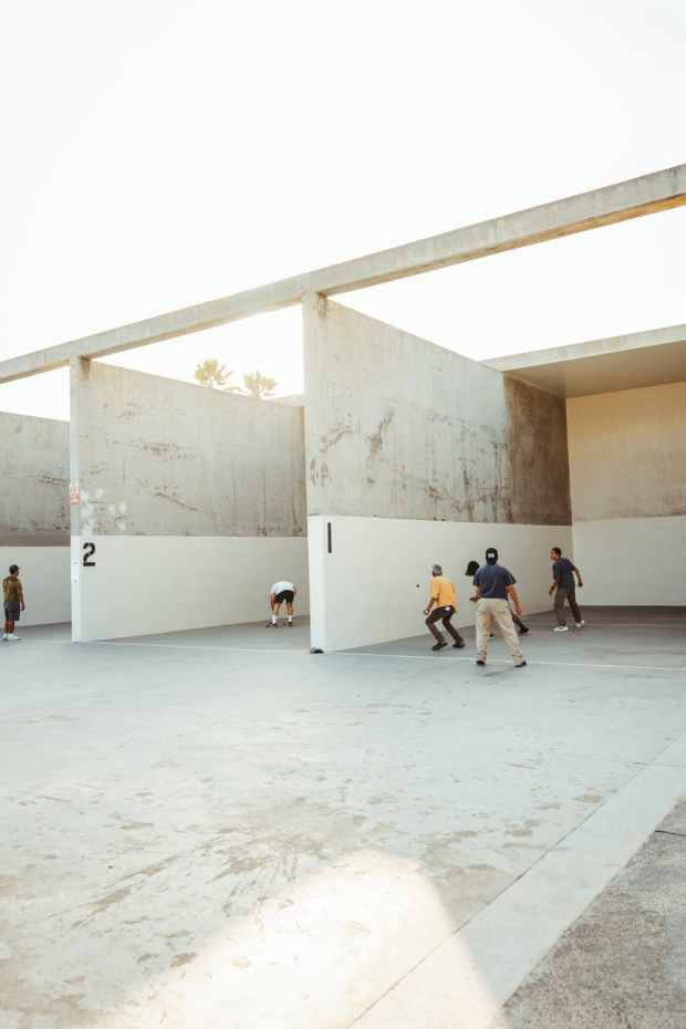anonymous athletes playing handball in outdoor courts in sunlight