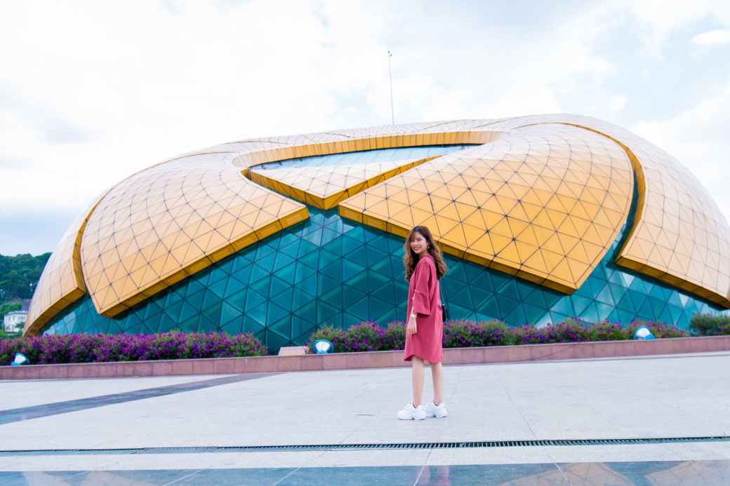 woman standing in front of yellow and blue glass building