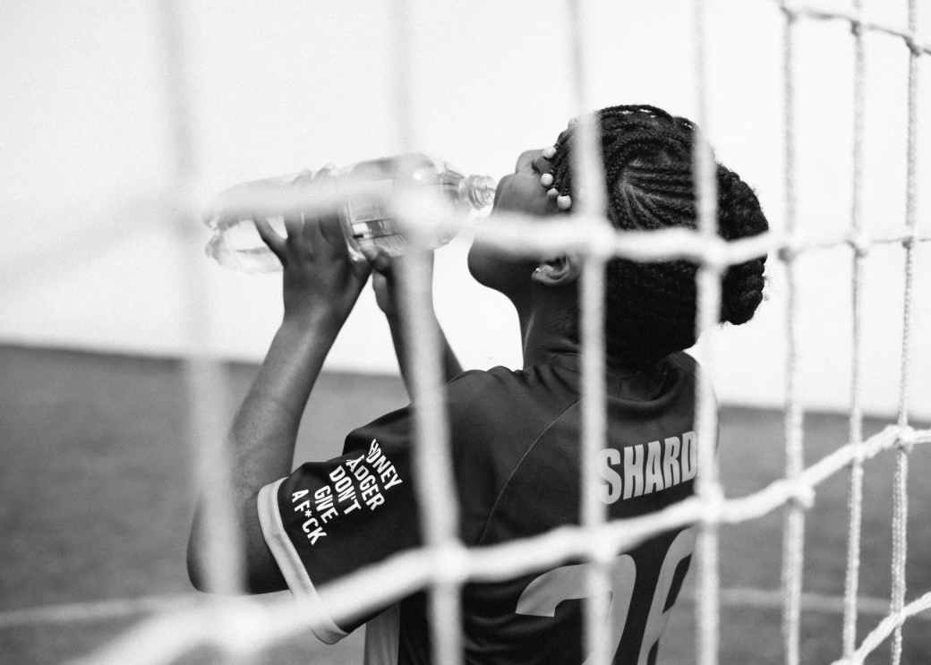 african american woman drinking while goalkeeping