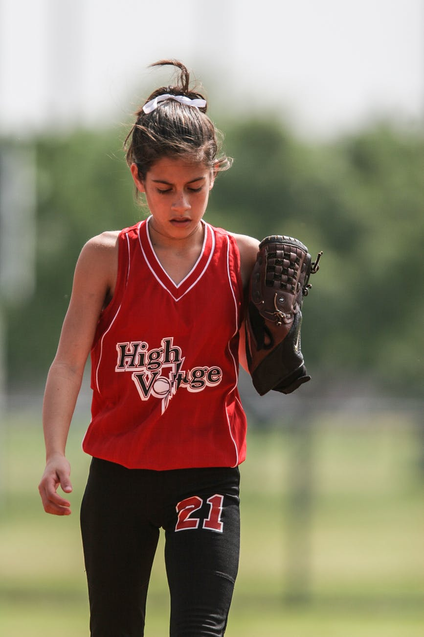 girl in red and black softball uniform walking