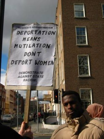 "somali man stands outside Dail in Dublin city holding up a sign that reads ""Deportation means mutilation don't deport women"""