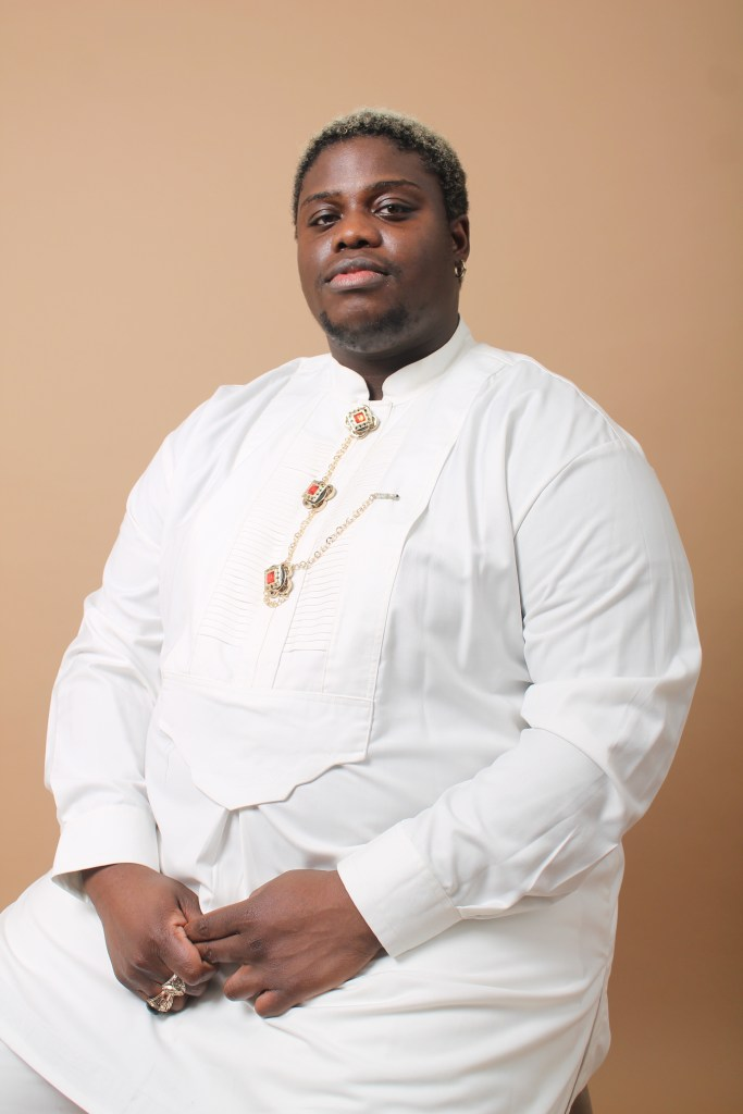 One person siting on a stool infront of a beige backdrop under studio lights, looking into the camera. Wearing white traditional attire and gold rings.