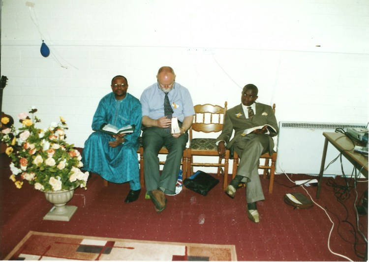 Three men in suits sit on church chairs holding bibles.