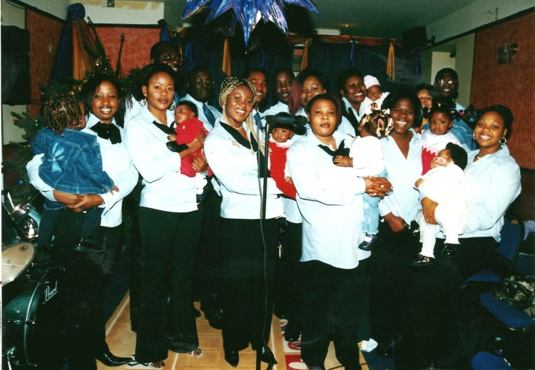 A row of women and men in blue shirts and black trousers pose on stage. The women near the front hold babies in red dresses.