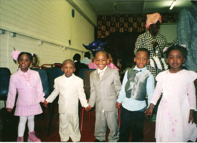 Four young children wearing dresses and suits hold hands while smiling into the camera.