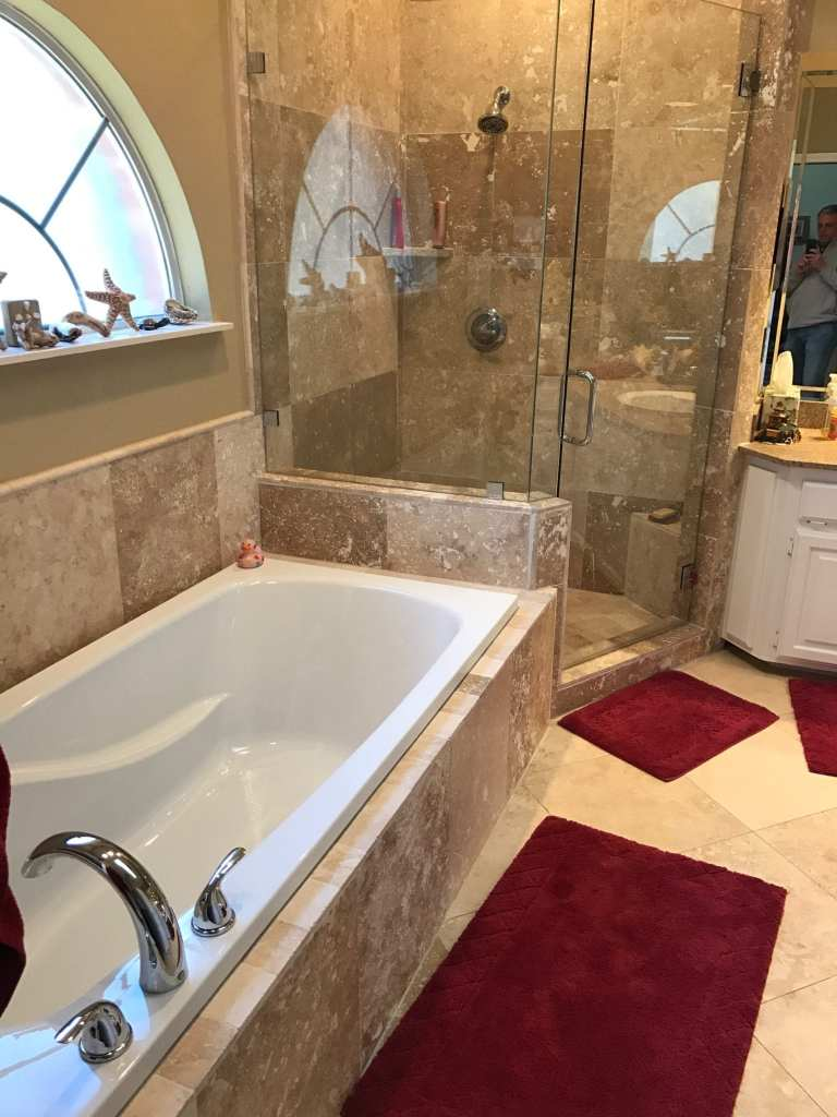 A bathroom remodeled with new tile walls, tile floor, shower glass, and paint.