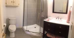 Bathroom remodeled with new wall and floor tile, shower tile, granite counters, vanity, paint, lights, and mirror.