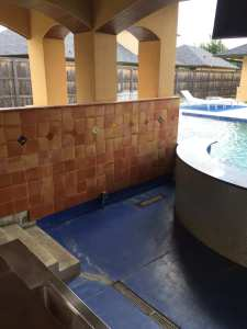 Outdoor pool bar tile installed on walls.