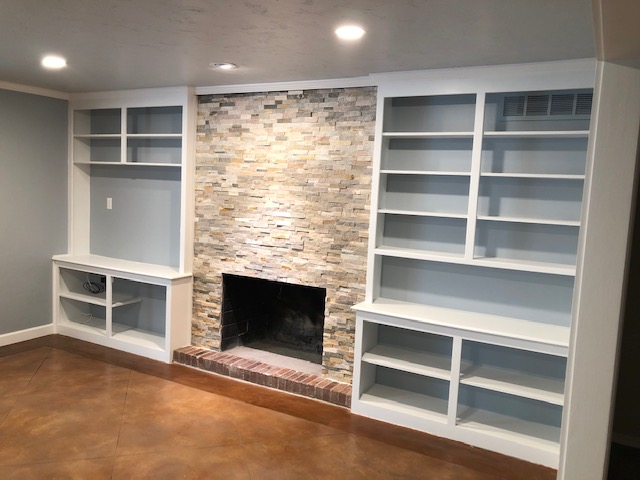 This remodeled living room includes new texture with a painted ceiling, walls, and bookshelves, a new stone exterior on the fireplace, and new LED lighting.