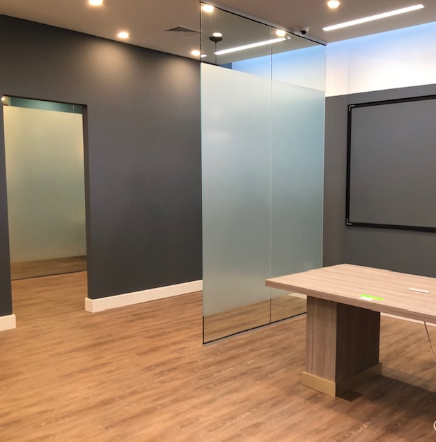 This commercial remodel includes a newly raised ceiling, lighting, flooring, and custom glass panels.