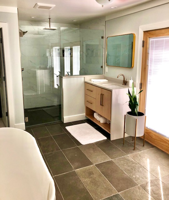 New master bathroom and closet addition. Walk-in shower with limestone tile floor and porcelain wall tile. Stand-alone deep tub. Custom-built vanities with quartz countertops.