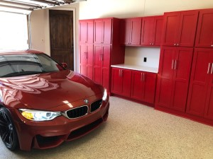 Custom built garage cabinets with quartz countertop and bright red paint!