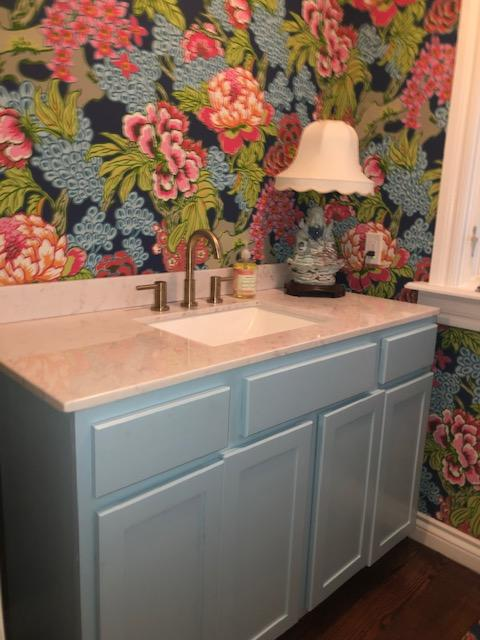 New guest bathroom with stained wood floors, new vanity and counter and toilet installed.