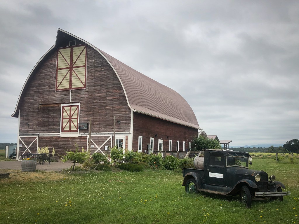 large barn with old car in front