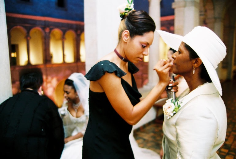 A tall Black woman makeup artist applies lip color to a Black mother of the bride.