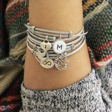 a wrist displaying several silver charm bracelets
