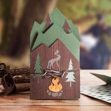 A handcrafted paper greeting card showing a campfire scene.