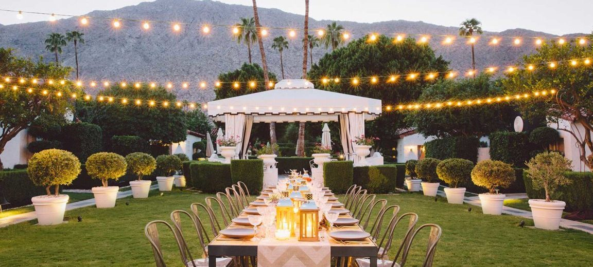 Image ID: a dining table set in the middle of a lawn, with twinkle lights strung above.