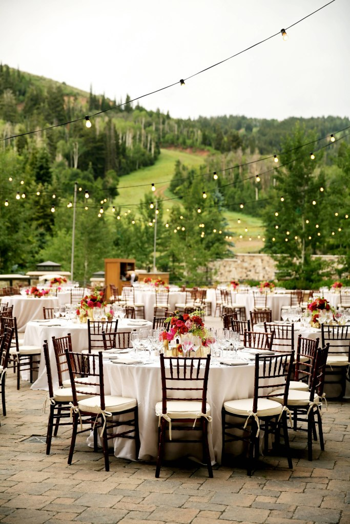 Outdoor photo of round tables with floral centerpieces