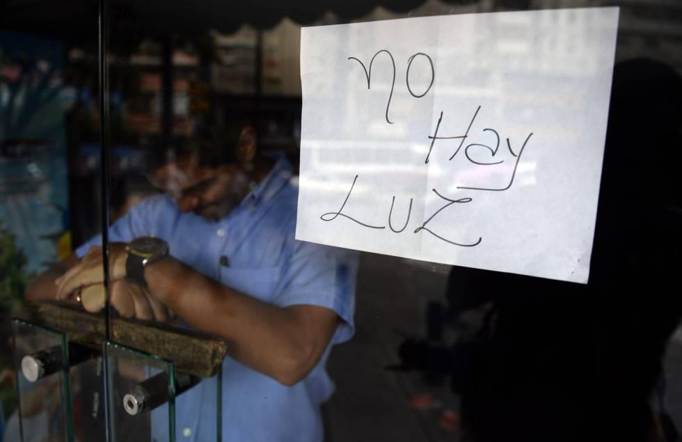 Un empleado, tras la puerta de un comercio cerrado en Caracas.