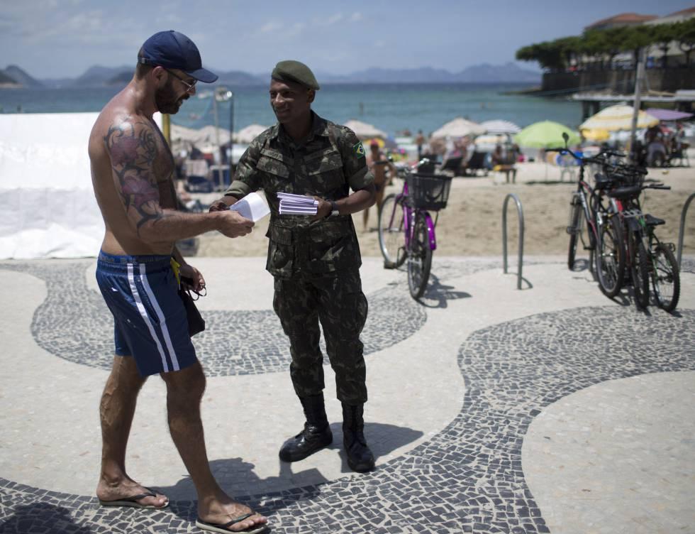 Un soldado reparte folletos informativos sobre el virus del Zika en la playa de Copacabana.