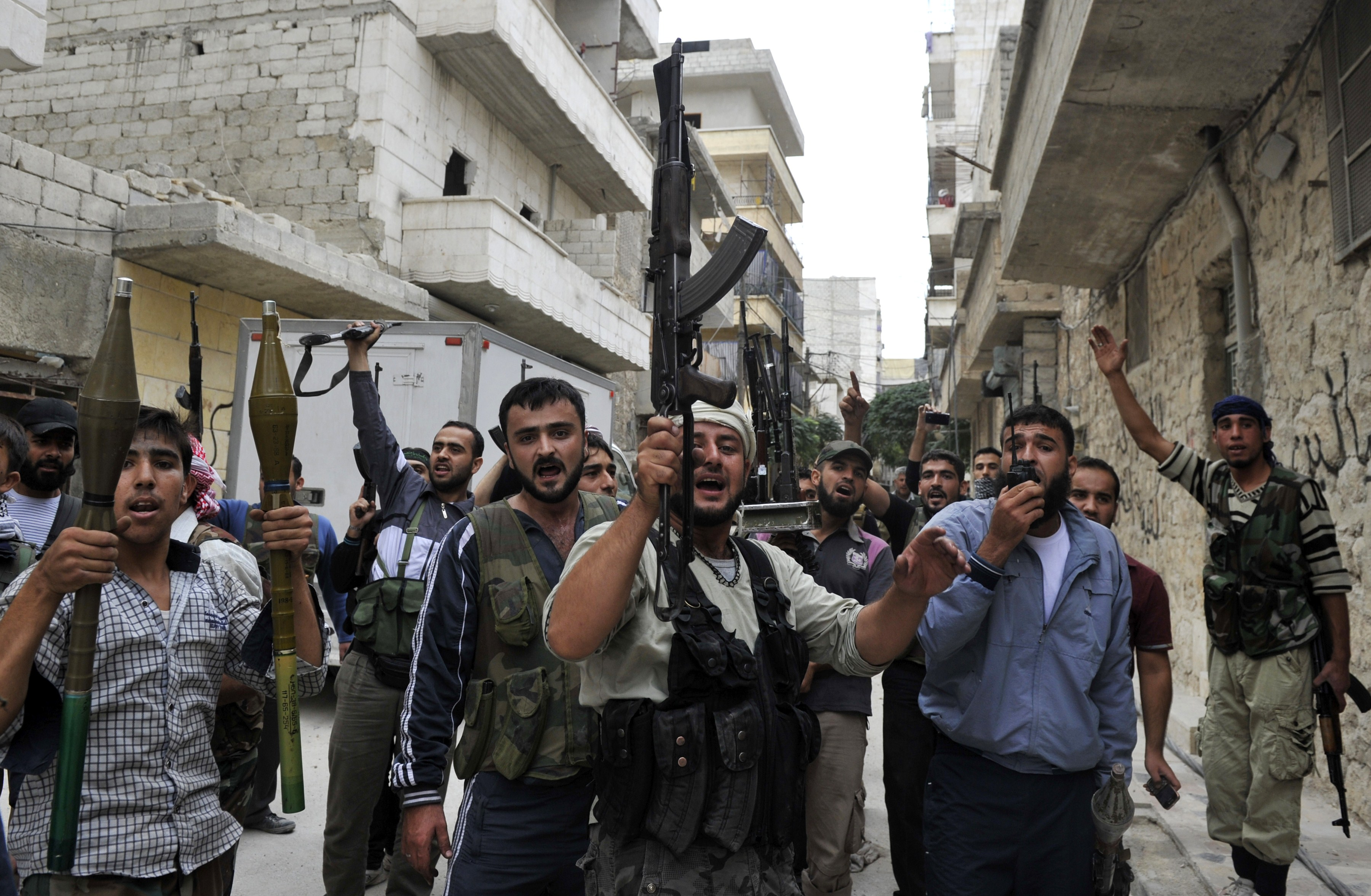 TO GO WITH AFP YEAR2012 BY HERVE BAR (FILES)- An October 11, 2012 file photo shows Syrian rebel fighters holding up their guns as they shout slogans in a street in the northern city of Aleppo following shelling by government forces. Syria's uprising has shifted from popular street protests against President Bashar al-Assad to a full-fledged war, increasingly influenced by armed Islamists, in a far cry from the idealism of the Arab Spring. AFP PHOTO/TAUSEEF MUSTAFA  YEAR2012-SYRIA-CONFLICT