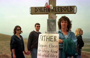 Gente visitando la zona donde se levantó un homenaje a las víctimas de la masacre de Columbine, en Littleton, Colorado. En la imagen, una cruz con la foto y el nombre de Dylan Klebold y una pancarta donde se lee: