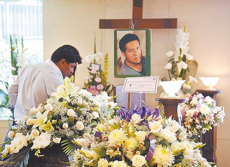 Velorio. Un amigo de Mauricio Calle Fernández, el joven pasante, se despide de él; fue ayer.