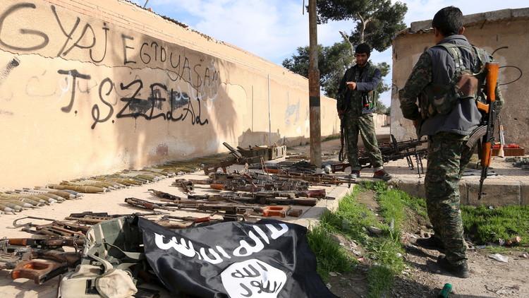 Miembros de las Fuerzas Democráticas de Siria examinan las armas y las municiones del Estado Islámico.