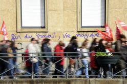 """Los manifestantes caminandelante de un graffiti donde se lee: """"fin del trabajo, la vida mágica"""" en la localidad de Rennes, Francia. DAMIEN MEYER (AFP)"""