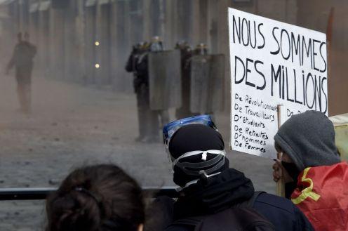 """Un manifestante sostiene un cartel de lectura """"Somos millones"""" mientras evitan a la policía antidisturbios en Rennes, Francia. DAMIEN MEYER (AFP)"""