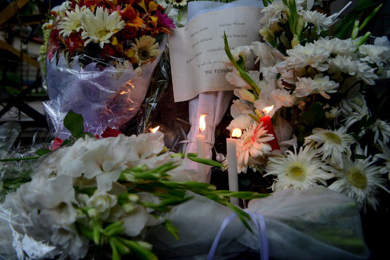 Candles and a sign bearing the names of some of the victims killed a bloody siege at an upscale cafe adorns one of many floral arrangements left near the restaurant in the Bangladesh capital Dhaka on July 3, 2016. Bangladesh began observing two days of national mourning July 3 after 20 hostages were slaughtered at a restaurant packed with foreigners in a terrifying escalation of a campaign of attacks by Islamist extremists. Seven Japanese nationals were killed in the attack. / AFP PHOTO / STR