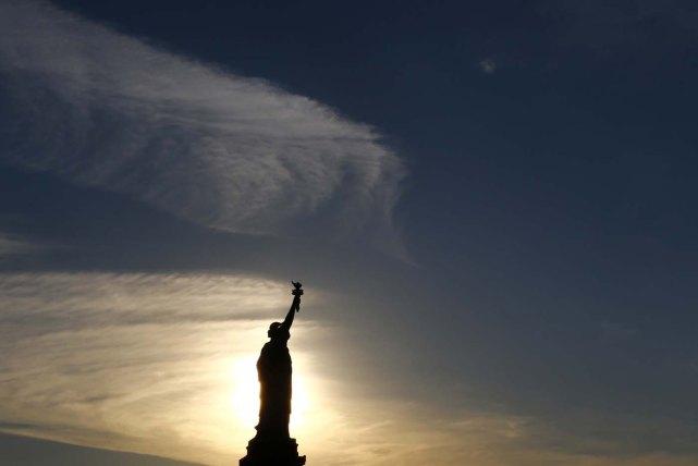 Vista del amanecer con la Estatua de la Libertad en primer plano, en la víspera del Día de la Independencia de Estados Unidos, el 3 de julio de 2016, en Jersey City, New Jersey. (AP Foto/Julio Cortez)