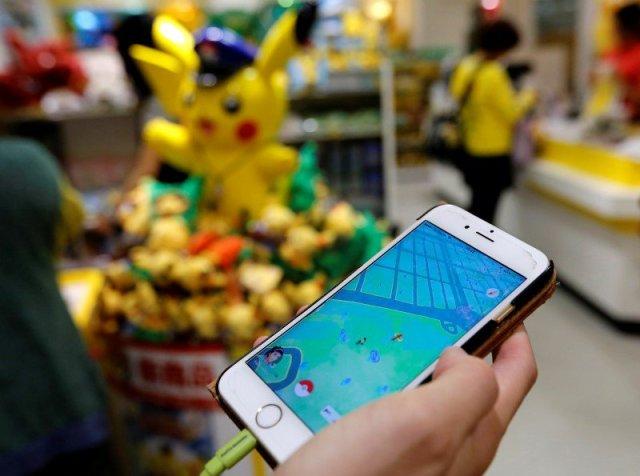 Un hombre juega Pokemon Go frente a una tienda que vende artículos de Pokemon, en Tokio, Japón. Foto: REUTERS/Toru Hanai