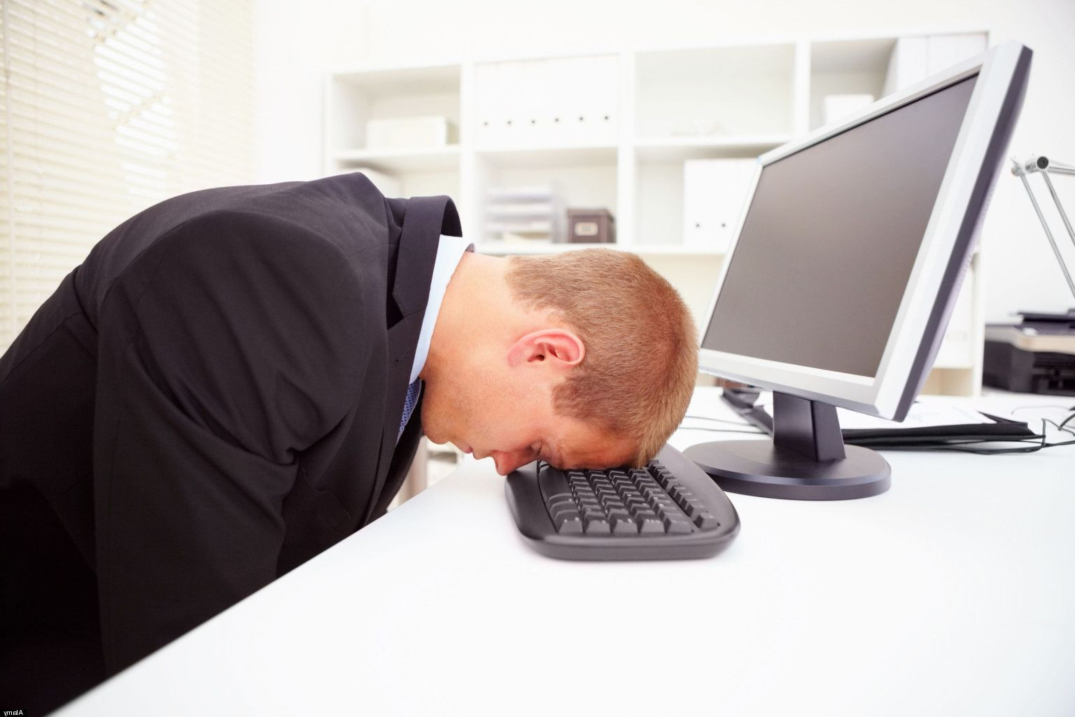 Portrait of a stressed businessman with his forehead resting on the computer keyboard