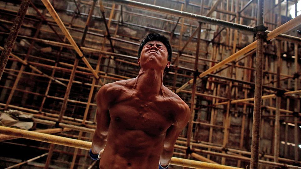 Shi Shenwei, realiza su rutina de barra fija, en un andamio de una obra de construcción en un templo budista, en el pueblo de Huangshan, cerca de Quanzhou, provincia de Fujian, China