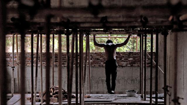 Shi Shenwei, realiza una rutina de barra fija en un andamio en la obra de construcción de un templo budista en el pueblo de Huangshan, cerca de Quanzhou, provincia de Fujian, China