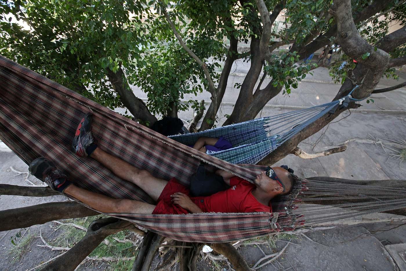 """ACOMPAÑA CRÓNICA: BRASIL VENEZUELA BRA08. BOA VISTA (BRASIL), 22/10/2016.- Los venezolanos José Antonio Garrido (d) y Sairelis Ríos (i) duermen en sus hamacas este jueves, 20 de octubre de 2016, frente a la terminal de autobuses de Boa Vista, estado de Roraima (Brasil). Es venezolana, tiene 20 años, quiere ser traductora y hoy, en una hamaca colgada en un árbol que ha convertido en su casa en la ciudad brasileña de Boa Vista, mece unos sueños que, según aseguró, no serán truncados por """"el fracaso de una revolución"""". """"No estoy aquí por política. Lo que me trajo aquí fue el fracaso de unas políticas"""", dijo a Efe Sairelis Ríos, quien junto a su madre Keila y una decena de venezolanos vive en plena calle, frente a la terminal de autobuses de Boa Vista, una ciudad que en los últimos meses ha recibido unos 2.500 emigrantes de ese país vecino. EFE/Marcelo Sayão"""