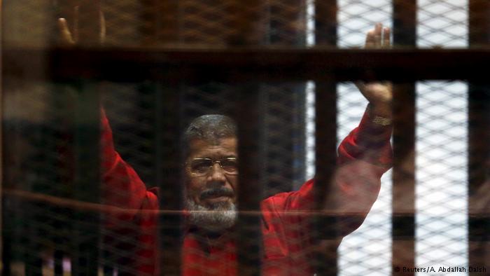 El expresidente egipcio, Mohamed Mursi, saluda a sus abogados y a la gente detrás de barras, luciendo el uniforme rojo designado a prisioneros sentenciados a muerte.
