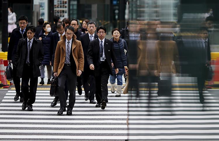 Varias personas cruzqan una calle del distrito financiero de Tokio, Japón, 22 de febrero de 2016